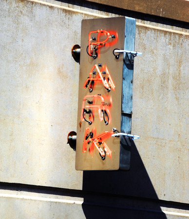 Parking garage flashes orange neon sign to advertise parking space.  Sign is attached to concrete wall.