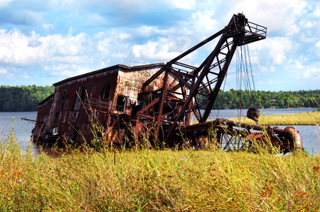 reclamation: Copper mining relic, reclamation suction dredge, leans heavily in the waters of Torch Lake outside of Mason, Michigan.  Weeds, rust and graffiti cover old mining equipment.