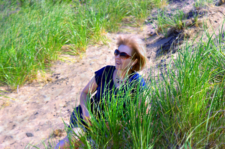 Adult female relaxes on the sand dunes on Lake Superior in Upper Peninsula, Michigan.  Tall grasses surround her and the wind tugs at her hair. Stok Fotoğraf