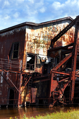 rusting: Rusting copper dredge leans into Torch Lake.  Abandoned and rusting, this mining equipment has been vandalized and graffitied. Stock Photo