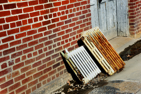 replaced: Old iron radiant heaters lay discarded against brick wall.  Heaters are being replaced by more up-to-date heating options.