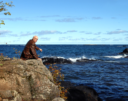 necessity: Retired man sits on Lake Superiors rocky shoreline in Upper Peninsula, Michigan.  He is sitting on a rocky cliff overlooking the deep blue water.  Cold Fall weather makes his coat a necessity. Stock Photo