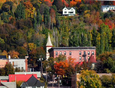 hancock: Scenic view of old Hancock Hotel with city street leading into beautiful Fall foliage.  Hancock is located in Upper Peninsula, Michigan. Stock Photo