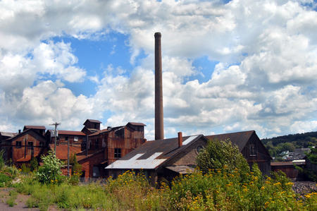 smokestack: Historic buildings and smokestack of the Quincy Copper Smelter in Ripley, Michigan is framed by overgrowth and blue skies. Stock Photo