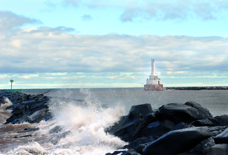 rushes: North Entry Light warns ships off the dark rocks of the Portage Canal on Lake Superior.  Rough water rushes against rocks as early morning lights sky. Stock Photo