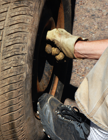 blow out: Mans hand bolts on a the spare tire after a blow out.  Sneaker clad foot holds pressure on bottom of tire.