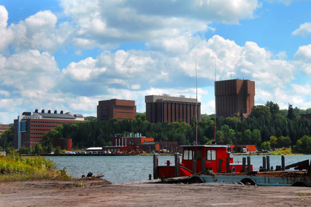 tug boat: Building on the Michigan Tech Campus are framed by blue sky.  Front of image shows bright red tug boat docked on the Portage Lake between Houghton and Hancock, Michigan.