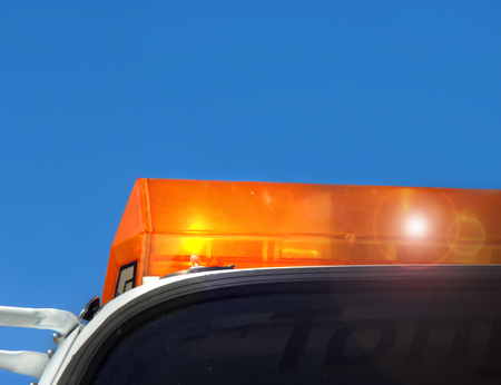 flat tire: Flashing yellow light tops an emergency response vehicle.  Tow truck responds to flat tire repair.