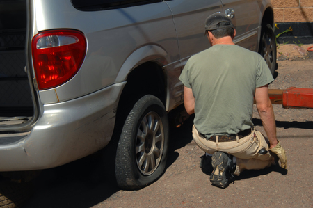 serviceman: Roadside assistance uses a tow truck lift to jack up the vehicle to replace a flat tire.  Serviceman is wearing an olive colored tee shirt and tan pants. Stock Photo