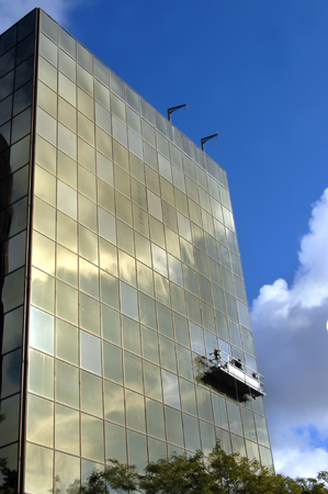 Scaffolding lifts workers cleaning exterior windows on a building in Hancock, Michigan.  Vivid blue sky and clouds are reflected in office window glass.