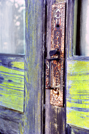 rusting: Aging door handle is made of metal and has been painted white.  Paint is worn and cracked and metal is rusting.  Door frame is rustic wood. Stock Photo