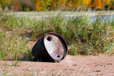 upper peninsula: Metal drum lays on the sand besides Lake Superior in Upper Peninsula, Michigan.  Fall foliage lines woods and lake can be seen beyond the dune grasses.