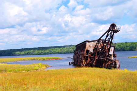 Abandoned copper reclamation suction dredge, sits in the waters of Torch Lake in Upper Peninsula, Michigan.  The mining equipment is rusting and sinking into the elements just outside of Mason, Michigan.