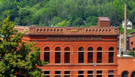 floor level: Historic Houghton National Bank sits in downtown Houghton, Michigan.  It is Richardsonian Romanesque style with Jacobsville sandstone on first floor level.