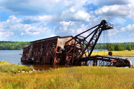 Copper reclamation suction dredge lies sideways in the waters of Torch Lake near Mason, Michigan.  Rusty and covered in graffiti, this relic from the mining industry is a local landmark.