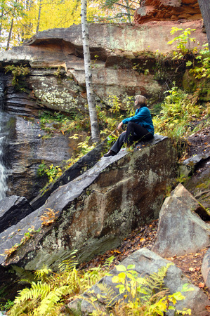 upper peninsula: Woman sits on large rock besides Hungarian Falls in Upper Peninsula, Michigan.  Autumn yellow colors background and leaves.