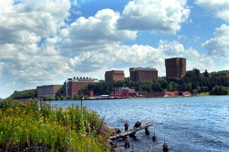 lake fronts: Flowers and dilapidated wooden dock fronts image of Michigan Tech in Houghton, Michigan.  Campus buildings overlook Portage Lake.