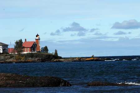 lake dwelling: Eagle Harbor Lighthouse sends out its beam of searching light across the Lake Superior deep dark water. Stock Photo