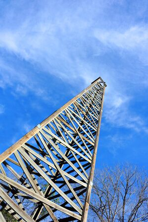 oil derrick: Rustic, wooden oil derrick is framed by blue sky and whispy clouds.
