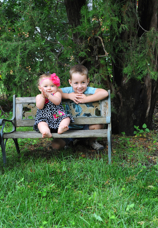 Sister and brother pose side by side.  Brother leans over back of park bench and sister sits on seat. Stockfoto