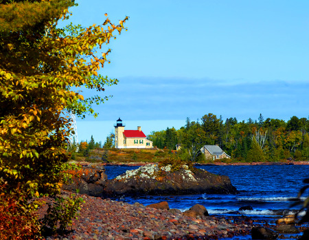 lake michigan lighthouse: Copper Harbor Lighthouse sits at the tip of the Keweenaw Peninsula in Upper Peninsula, Michigan.  Visitors can be seen walking the steps to view the lighthouse.