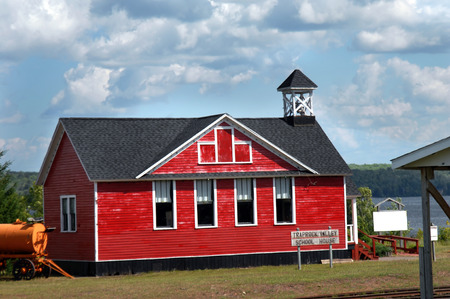tilo: Red, wooden, one-room school house sits besides Lake Linden in Lake Linden, Michigan.