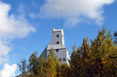 oudoors: Quincy Copper Mine 2 Shaft Rock House rises above golden leaves of autumn and is outlined by vivid blue sky.  Building is part of the copper industry in Upper Peninsula, Michigan. Stock Photo