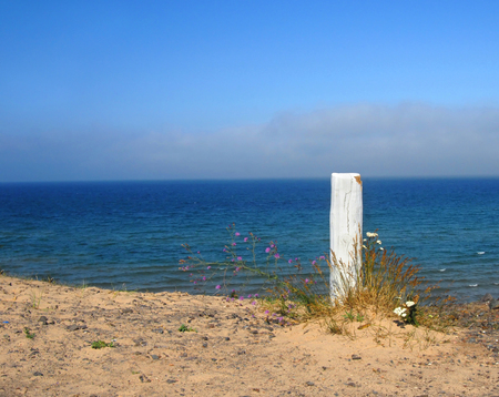 sea grass: Sea grass and wildflowers surround rustic wooden post sitting on bluff overlooking Lake Superior on the Keweenaw Peninsula.
