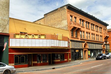 shut down: Old movie theater called LODE, is closed and shut down permanently.  City street is bricked and only a few cars are parked in downtown Houghton, Michigan. Editorial