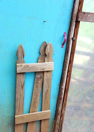 green door: Greenhouse door has wooden picket fence attached.  Door is painted torquoise. Stock Photo