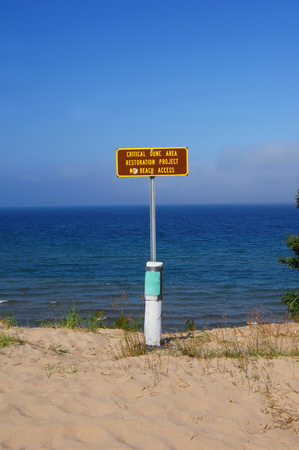 visitors area: Sign warns visitors to stay away from the Dune Restoration Area.  Sign sits on top of rustic, white post on a beach at Lake Superior in Michigan. Stock Photo