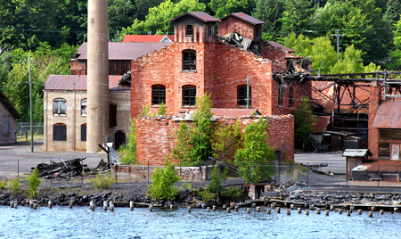 smelter: Historic Quincy Copper Smelter lays abandoned and empty.  Buildings have fallen into ruin with rusting metal and broken windows.  Smelter sits on the shore of the Portage Lake near Hancock, Michigan.