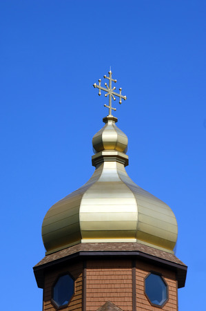 byzantine: Golden colored dome and cross shaped finial tops the Byzantine Rite Catholic Monastery near Eagle River, Michigan.