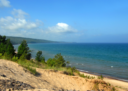 curving: Curving shoreline disappears into the distance on Lake Superior in the Upper Peninsula of Michigan.  Blue sky, blue water and sandy dune complete landscape. Stock Photo