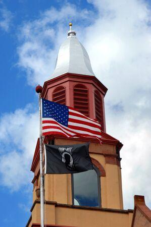 octagonal: cúpula octogonal y cubierta ornamental, en la Estación Village Hall and Fire Lake Linden, está enmarcado por el cielo azul y las nubes. Una bandera de POW y bandera de Estados Unidos vuela en la pole además de él.