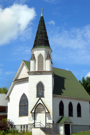 hancock building: Green roofed Church of Christ, has conical shaped steeple with cross finial.  Building is white.  Historic church isin Hancock, Michigan. Stock Photo