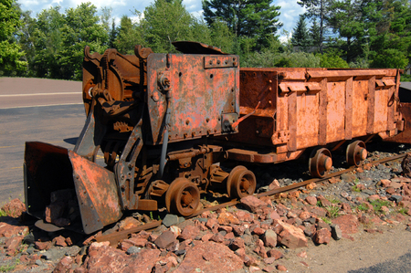 rusting: Rusting ore loader, sits on section of train track in the old Copper mining district of Upper Peninsula, Michigan.  Loader once transported copper ore for mines. Stock Photo