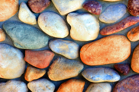 River rocks cover wall in a miriad of colors.  Each rock is a different color and shape.