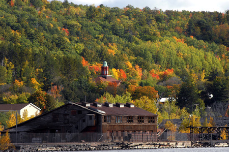 rusting: Autumn image of the Historic Quincy Copper Smelter.  Buildings are rusting and windows broken.  Abandoned Smelter sits on the shore of Portage Lake with Quincy Hill rising in background.