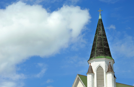 surrounds: Background image shows steeple of the Church of Christ in Hancock, Michigan.  Steeple is conical shaped with cross finial.  Blue sky surrounds steeple.