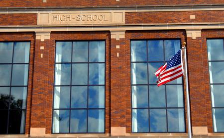 """Amerikaanse vlag vliegt in de voorkant van een middelbare school gebouw. Windows weerspiegelen wolken en blauwe hemel en de woorden """"high school"""" is gegraveerd op de voorkant van het gebouw."""