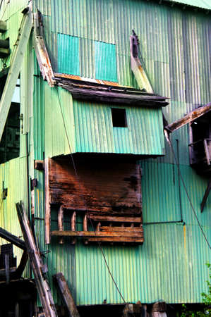 upper peninsula: Derelict shaft house, is a fast declining relic of the Copper Mining industry in Upper Peninsula, Michigan.  This shaft house is green sheet metal with wooden supports.