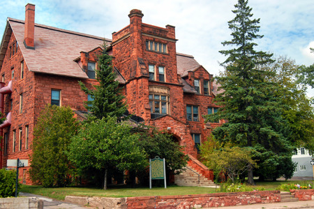 buttresses: Old Main, on the Finlandia College Campus, is an historic building built out of Jacobsville sandstone locally quarried in the Upper Peninsula.  It has gabled roof, dormers and a tower.