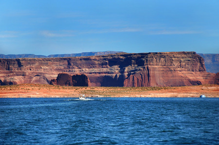 lake powell: Speedboat takes in the view of the red sandstone cliffs surrounding Lake Powell.  Cliffs show size comparison with houseboat docks besides it. Stock Photo