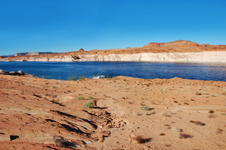 houseboat: Houseboat is docked along the beautiful sandstone rocks and cliffs of the Glen Canyon National Recreation Area in Arizona.