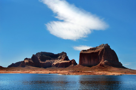 steep cliffs: Beautiful and steep cliffs line the shores of Lake Powell.  Blue skies and lake water frame the red formations. Stock Photo