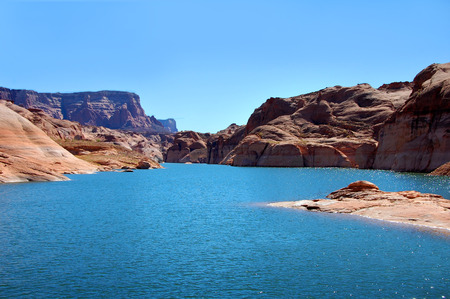 lake powell: Aqua waters of Lake Powell curve away into the distant Glen Canyhon National Recreation Area.  Rock mounds and steep cliffs rise on either side. Stock Photo