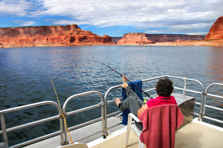 houseboat: Woman relaxes and enjoys the fantastic views of sandstone cliffs and blue skies.  She is on a houseboat on Lake Powell in Arizona.  She fishes holding the rod with her toes. Stock Photo