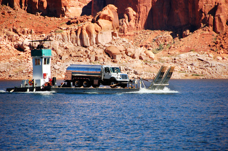 lake powell: Tugboat transports barge loaded with a tanker truck on Lake Powell in Arizona.