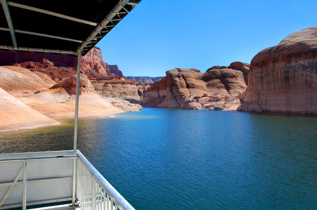 lake powell: This houseboat has a view!  Beautiful sandstone rocks and steep cliffs tower over Lake Powell and its waterway.